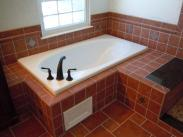A new soaking tub with decorative tile work around the wall and an easy access panel