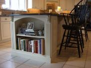 Elegant built in book shelves in the center island make access to recipes easy